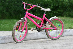 Pink bicycle. A secured, locked pink bicycle standing in a nature park Stock Photos