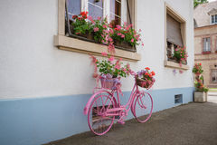 Pink bicycle with flower baskets on street Stock Photography