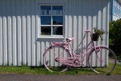 Pink bicycle in front of white house in Sweden Stock Photo