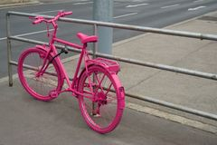 Pink bicycle locked to the railing. Pink painted bicycle locked to the railing royalty free stock photo