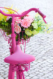 Pink Bike. Detail of a pink painted bicycle with a basket with flowers and leaves Royalty Free Stock Photo