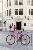 A pink bike in Auckland City. With a lady in the background. Theme of pink royalty free stock photo