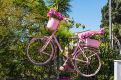 Pink bike with flowers hung on a fence in Alghero Stock Photos