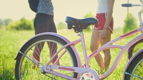 Pink bike on the green grass in the background communicate two young cyclists. Telephoto shot stock video footage