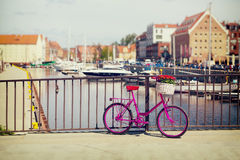 Pink bike standing on a bridge. Near harbour in Gdansk, Poland, with boats and buildings in the background, vintage colors stock photography