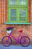 Pink bike standing by the wall. Pink bike with white basket full of flowers standing by the brick wall next to green windows Royalty Free Stock Image