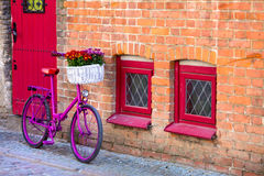 Pink bike standing by the wall. Pink bike with white basket full of flowers standing by the brick wall next to red door and windows Royalty Free Stock Photo