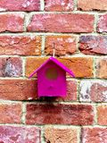 Pink bird house. Pink small bird house on the brickwall Royalty Free Stock Photo