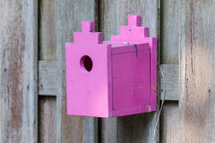 Pink birdhouse on a wooden fence Royalty Free Stock Images