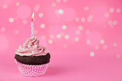 Pink birthday cupcake with lights. Pink birthday cupcake with a candle and lights effect at the background Royalty Free Stock Images