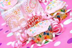 Pink birthday party cupcake with gift. Pretty pink iced cupcake with a Happy Birthday pick, ribbons around and party present in the background Stock Photos