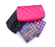 Pink and black cosmetic bags and palettes of colored eyeshadow for makeup. Pink and black cosmetic bags and palettes of colored eye shadow for make up isolated royalty free stock photography