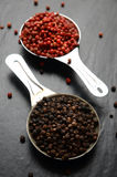 Pink and black peppercorns on a spoon Stock Photo