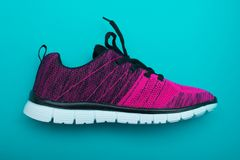 Pink and black sport woman shoes  on turquoise background. Royalty Free Stock Photography