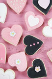 Pink, black and white homemade heart shape cookies on vintage shabby chic pink wood background Stock Images