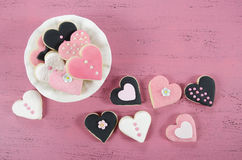 Pink, black and white homemade heart shape cookies on vintage shabby chic pink wood background. For Valentines Day, wedding, Mothers Day or female birthday Royalty Free Stock Photo