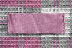 Blank clothes label. Pink blank clothes label on checkered textile background closeup stock images