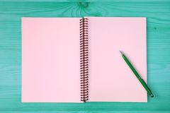 Pink blank page of an opened notebook and a green pen on the blue green wooden table royalty free stock photography