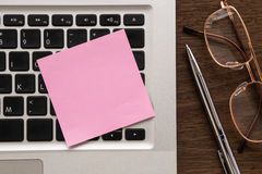 Pink blank paper on laptop for note Royalty Free Stock Photo