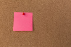 Pink Blank sticky notes red pinned into brown corkboard. close up stock images