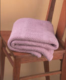 Pink blanket folded on wooden chair Royalty Free Stock Photos