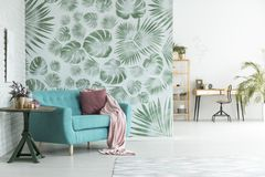 Floral room with workspace. Pink blanket and pillow on blue settee next to a table with plant in room with workspace and floral wallpaper Stock Images