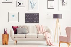 Pink living room with posters. Pink blanket on a sofa between lamp and wooden stool in living room interior with posters and chair Royalty Free Stock Images