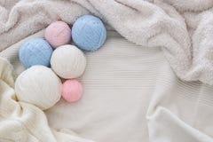 pink& x27; blaue und weiße warme und gemütliche Garnbälle der Wolle über weichem Bett stockbild