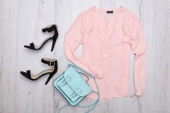 Pink blouse with a tag, black shoes, mint bag. Fashionable concept. Wooden background Stock Photos
