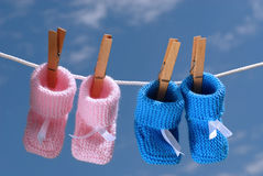 Pink & blue baby booties hanging on a clothes line. Pregnancy concept: pink & blue baby booties hanging on a clothes line against a blue sky stock photography