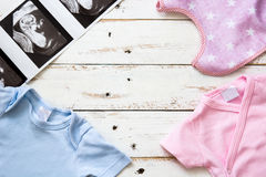 Pink and blue baby romper and ultrasound on white wood Royalty Free Stock Photo