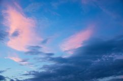 Pink and blue clouds in the sunset sky royalty free stock photography