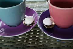 Pink and blue color coffee, tea cups with merengue. Pink and blue color coffee, tea cups with two merengues in braided table stock photo