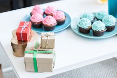 Pink and blue cupcakes and gift boxes on white table,. Baby-party concept royalty free stock image