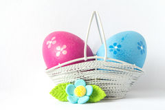 Pink and blue Easter eggs in a basket with blue flower Royalty Free Stock Photos
