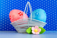 Pink and blue Easter eggs in a basket with pink flower Royalty Free Stock Images