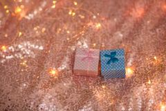 A pink and blue gifts on a coral shiny background. royalty free stock image