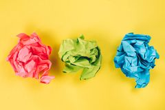 Pink, blue and green crumpled paper balls on bright yellow background stock photos