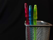 Pink blue and green pens on a black background royalty free stock photos