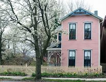 Pink & Blue House with Picket Fence & Flowering Pear Tree Royalty Free Stock Image