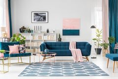 Pink and blue living room. Patterned carpet in pink and blue living room interior with sofa against white wall with painting royalty free stock image