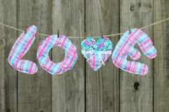 Pink and blue LOVE text and heart hanging on clothesline by shabby wooden fence Royalty Free Stock Photos