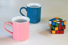 Pink and blue mugs and a puzzle. Pink and blue mugs filled with water and a puzzle Royalty Free Stock Photo