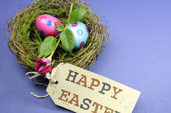 Pink and blue polka dot eggs with rose bud in nest. With Happy Easter gift tag Royalty Free Stock Image