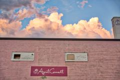 Pink Blue Sky and Building. A pink cloudy sky with a pink building in the foreground. Saturated pastel colors and inviting environment. Located in Burlington stock photography