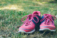 Pink and blue sneakers on a green grass Royalty Free Stock Photo