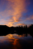 Pink and Blue Sunset and Trees Reflected in Alpine Lake. Royalty Free Stock Image