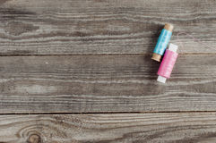 Pink and blue thread reels. On wooden background Stock Photo