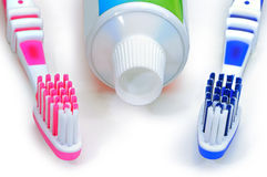 Pink, blue toothbrushes and toothpaste isolated on a white backg Royalty Free Stock Images