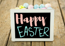 Pink and blue type on tablet on wood table with easter eggs Royalty Free Stock Photo